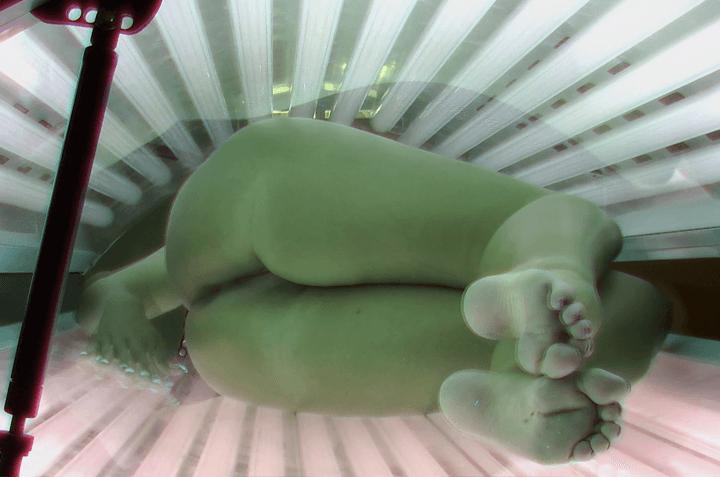 Spanneraufnahme von nacktem Arschluder auf der Sonnenbank